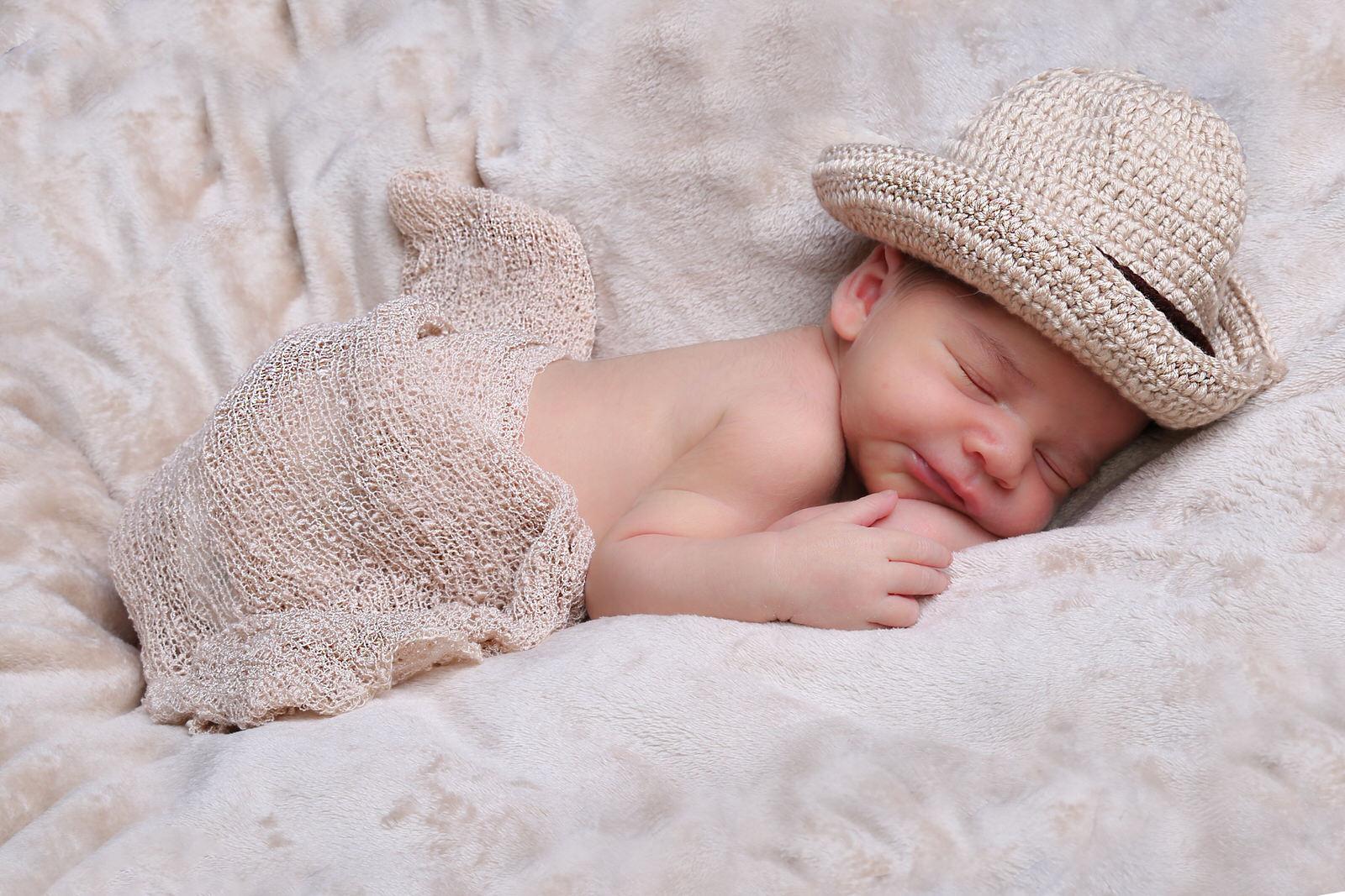 newborn foto neonato con cappello addormentato